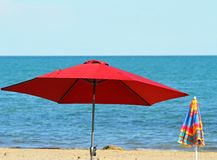 Red beach umbrella on the beach and the blue sea Stock Images
