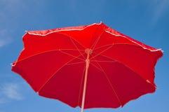 Red beach umbrella and blue sky Stock Image