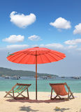 A red beach umbrella and chaise lounges Stock Images