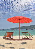 Red beach umbrella and deck chairs Stock Photos