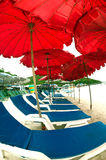 Red beach umbrella and deck chairs on the beach. Stock Images
