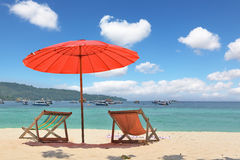 Red beach umbrella and deck chairs on the sand Stock Photo