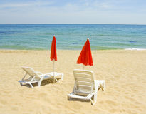 Red beach umbrellas and white chaise longues Royalty Free Stock Photo
