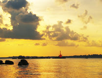 Red Beacon. Navigation safety beacon positioned on rocky outcrop in a narrow waterway between islands and the mainland, taken at sunset Royalty Free Stock Image