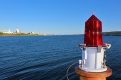 A red beacon light on a cement platform in the Strait of Canso near Port Hawkesbury Nova Scotia. A summer scene from the shoreline of Nova Scotia, Canada Stock Image