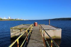 A red beacon light on a cement platform in the Strait of Canso near Port Hawkesbury Nova Scotia. A summer scene from the shoreline of Nova Scotia, Canada Stock Photography