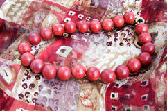 Red bead necklace on a silk scarf Royalty Free Stock Images
