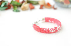 Red beaded bracelet with floral print. On a textile background Royalty Free Stock Photo