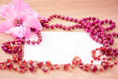 Red beaded necklace & flower with empty card Royalty Free Stock Image
