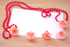 Red beaded necklace & flowers with empty card Royalty Free Stock Photos