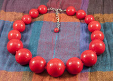 Red beads. Handmade red beads for women on coloured background Stock Images