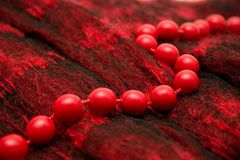 Red beads. Lay on a woolen female scarf Stock Photo