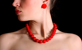 Red beads around  neck of beautiful girl. Red beads and a round shackle around  neck of beautiful girl Royalty Free Stock Photo