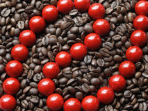 Red beads in brown beans Royalty Free Stock Photography