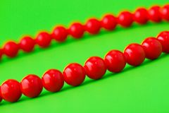 Red beads on green background Stock Images
