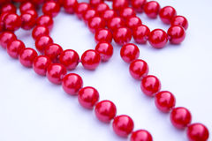 Red beads lie on a white background Royalty Free Stock Image