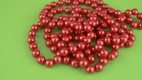 Red beads necklaces on green background isolated. Red beads necklaces on green background for female person stock video