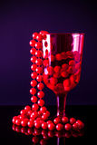Red beads in red glass Royalty Free Stock Photography