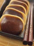 Red bean cakes. Traditional red bean cakes on plate with chopsticks on table mat Royalty Free Stock Photo