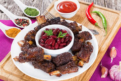 Red beans in bowl surrounded by grilled ribs Stock Image