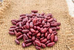 Red beans in burlap sack on wooden background Royalty Free Stock Image