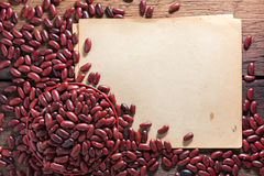 Red beans in a cup on a wooden floor. Red beans in a cup with notebook on a wooden floor Royalty Free Stock Photos