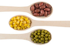 Red beans, green peas, sweet corn in wooden spoons Stock Photography
