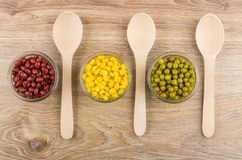 Red beans, sweet corn, green peas and wooden spoons Stock Photography