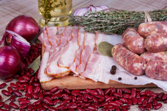 Red beans, thyme, sausages and bacon on wooden background. Royalty Free Stock Images