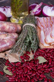Red beans, thyme, sausages and bacon on wooden background. Royalty Free Stock Image