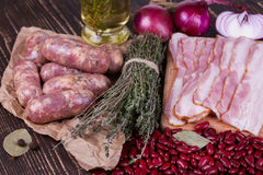 Red beans, thyme, sausages and bacon on wooden background. Royalty Free Stock Photos