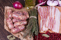 Red beans, thyme, sausages and bacon on wooden background. Royalty Free Stock Photo