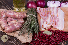 Red beans, thyme, sausages and bacon on wooden background. Royalty Free Stock Photography