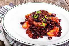 Red beans, tomatoes, ketchup, onion and spices on the white plat Stock Photos
