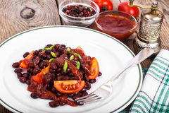 Red beans, tomatoes, ketchup, onion and spices on the white plat Stock Images