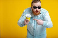Red beard man holding cup with coffee. Indignant red beard man in sunglasses and denim shirt holding paper cup with coffee. what is it Stock Image