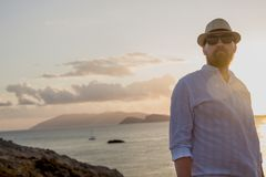 Red-bearded man of European appearance in the golden rays of the sun is at dawn against the backdrop of the sea and islands. Silhouette of a man in white Stock Photography
