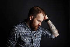 Red bearded man with tattooes studio portrait on dark background Stock Image