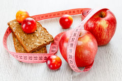 Red beautiful apples and plums meter tape Royalty Free Stock Images