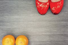 Red beautiful chinese oriental shoes and mandarine oranges. stock photo
