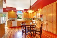 Red beautiful large kitchen with cherry hardwood. Stock Photo