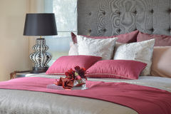 Red bed and pillows with plant in glass vase on tray Stock Photo