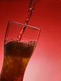 Red beer. Pouring beer in backlight over red background royalty free stock photos