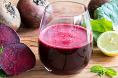 Red beet juice in a glass on a wooden background Stock Photos