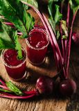 Red beet juice and gin cocktails on rustic background. Red beet juice in tall glasses on dark rustic background royalty free stock photography