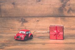 Red beetle car are dragging red gift box on old and vintage rust