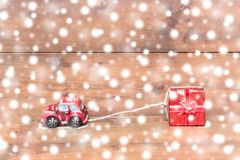 Red beetle car are dragging red gift box on snowing Stock Photos