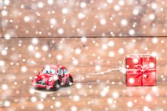Red beetle car are dragging red gift box on snowing on old and r. Ustic wooden background. using for Christmas greeting card, New Year and happy birthday present Royalty Free Stock Image