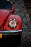 Red beetle front headlight. A front view of an old red volkswagen beetle, parked in front of a stone wall Royalty Free Stock Photos