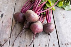 Red Beetroot with herbage green leaves on rustic background. Org Royalty Free Stock Photos